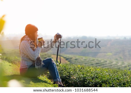 Asian Woman drinking beverage tea and take a photo,  relaxing and sitting outdoor in the tea plantation in sunshine light enjoying life her warm morning at balcony. Lifestyle Concept #1031688544