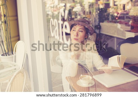 Asian woman drinking coffee and using computer in cafe. Photo filter effect. Selective focused
