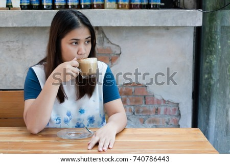 Asian woman drinking coffee in the cafe #740786443