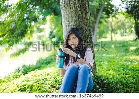 Asian woman drinking coffee while sitting in the park,Asia, Thailand, Adult, Adults Only, Beautiful People