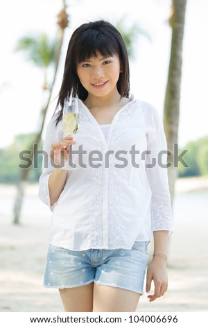 Asian woman drinks champagne on a tropical beach - stock photo