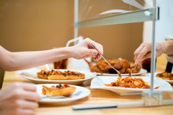 Asian woman eating food while siting separate and keep distance with table plastic shield partition in restaurant, new normal, restaurant, coronavirus outbreak and social distancing concept