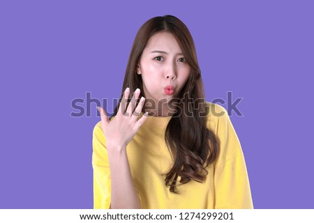 Asian woman eating hot and spicy food, yellow t-shirt clothing, purple background
