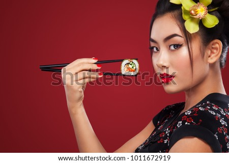 Asian woman eating sushi and rolls on a red background. International Women's Day, Black Friday, Setsubun Japanese Festival, sushi sale.