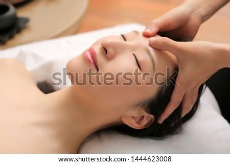 Asian woman enjoying facial spa massage with closed eyes #1444623008