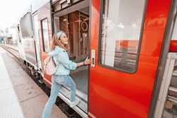 Asian woman entering wagon of a train. Railway transport concept