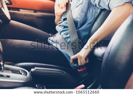Asian woman fastening seat belt in the car, safety concept - Shutterstock ID 1065512660