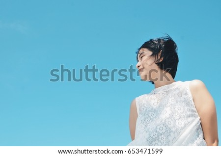 Asian woman feeling happy with copy space on blue sky background,summer concept