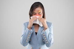 Asian woman feeling unwell because of sinus symptoms on a gray background. Businesswoman in blue suit blowing nose in a tissue. Dust mite allergy. Cold and Flu