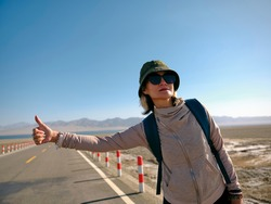 asian woman female backpacker traveling by hitchhiking