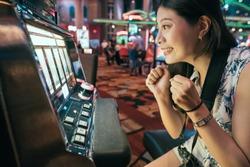 Asian woman gambling in casino playing on slot machines spending money. Gambler addict to spin machine. girl having fun playing game during holidays in las vegas.