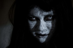 Asian woman ghost or zombie horror creepy scary close up she face and hair covering the face her eye looking to camera, Halloween day concept, in dark tone