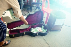 asian woman giving money into the guitar box for the performing of music band at the local street market of Thailand