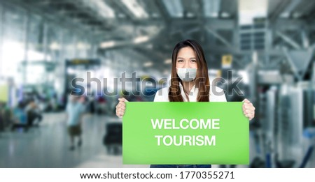 Asian woman guide tour hold welcome greeting banner for show to tourism in airport after coronavirus pandemic open lock down. Сток-фото ©