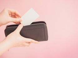 asian woman hand hold and bring out card in her blue purse with pink pastel background