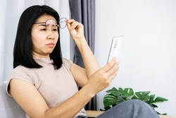 Asian woman hand holding  eyeglasses having problem with farsighted trying to read text on smart phone with eye sight blurred vision