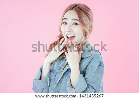 Asian woman happy with special deals & discounts of promotions, blue jean clothing, pink background