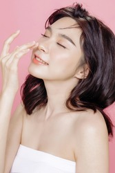 Asian woman has a lovely face is feeling happy with her perfect skin touch her face. She wears a white strapless bra. isolated over pink background. Skincare, cosmetology and plastic surgery concept.