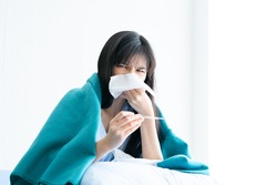 Asian woman has runny nose sits on hospital bed for cold flu treatments. Female patient checking how high fever she has using thermometer. White background copy space.