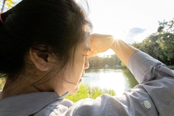 Asian woman have conjunctivitis,cataract,young female covering face by hand of bright sun in outdoor on sunny day,feel dizzy,risk of eye damage from ultraviole(UV rays),photophobia,eye health concept
