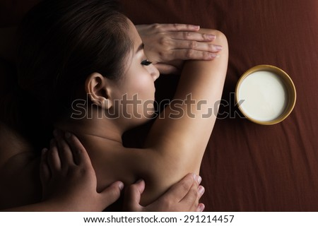 Asian woman having massage and bowl of milk , spa salon Beauty treatment