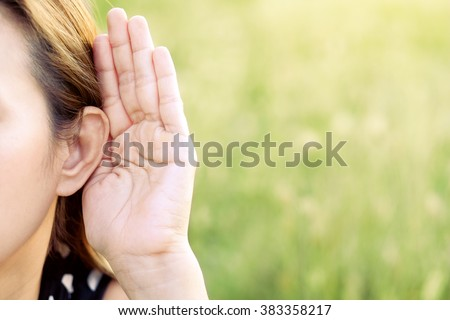 Asian woman hold her hand near her ear and listening in green field