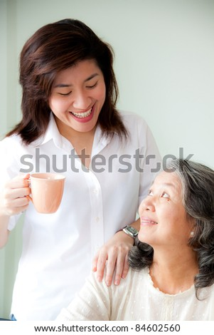 asian woman holding a cup looking senior woman