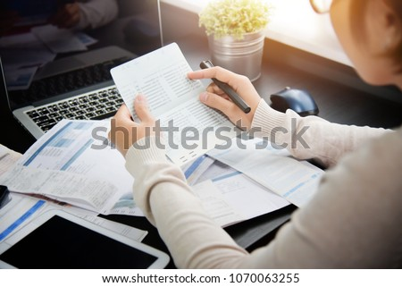Asian woman holding and looking to saving account book, bill and calculating her monthly expenses and Debts at her house.