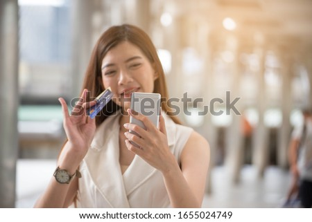 Asian woman holding credit cart and using tablet to shopping online.Shopaholic girl selecting products to cart in online website And pay via internet banking.