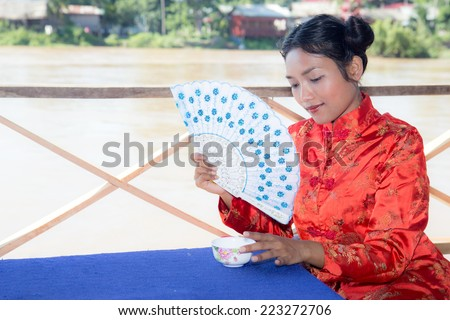 Asian woman holding fan and cup