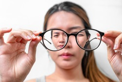 Asian woman holding glasses on white background, Selective focus on glasses , myopia and eyesight problem concept.
