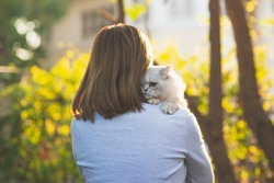 Asian woman holding her cat in the light of sunset