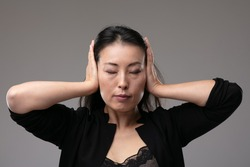Asian woman holding her hands covering her eyes with an inscrutable expression and eyes closed in a concept of the metaphor see no evil, hear no evil speak no evil, over a grey studio background