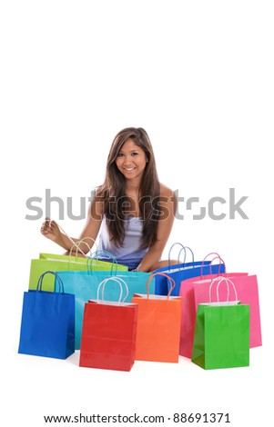 Asian woman holding receipt sitting with a bunch of colorful shopping bags