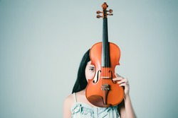 Asian woman holding violin in hand. Beautiful woman playing violin on grey background.