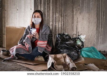 Asian woman homeless wearing hygiene face mask for protective infection and pandemic of coronavirus or covid19. Female beggar wearing sweater and blanket sitting hold bowl for help on walkway street Foto stock ©