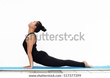 Asian woman in black dress doing yoga on blue mat on white background,Upward dog,Urdhva Dhanurasana