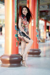 Asian woman in Cheongsam dress leaning against a pole at Chinese Shrine .