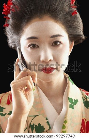 Asian woman in ethnic clothes talking on her cell phone