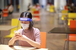 Asian woman in face shield,medical face mask outbreak,. Having absent-mindedness or depression that results from status pandemic risk Corona virus disease COVID-19 infection. Concept new normal.
