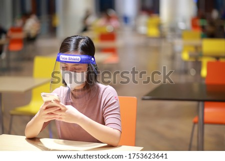 Asian woman in face shield,medical face mask outbreak,. Having absent-mindedness or depression that results from status pandemic risk Corona virus disease COVID-19 infection. Concept new normal. Stock photo ©