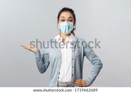 Asian woman in glasses and face mask introduce new company product or banner, pointing, holding promo on hand over left side copy space