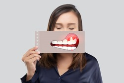 Asian woman in the dark blue shirt holding a paper with the broken tooth cartoon picture of his mouth against the gray background, Decayed tooth, The concept with healthcare gums and teeth