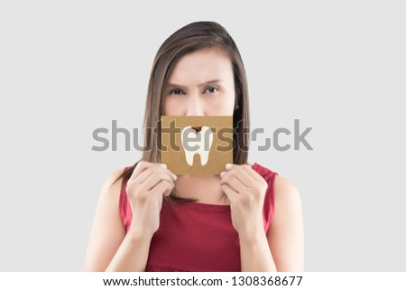 Asian woman in the red shirt holding a brown paper with the caries cartoon picture of his mouth against the gray background, Have a toothache, The concept with healthcare gums and teeth