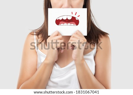Asian woman in the white wear holding a white paper with the broken tooth cartoon picture of his mouth against the gray background, Decayed tooth, The concept with healthcare gums and teeth
