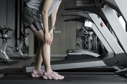 Asian woman injuries during workout in fitness gym. Young woman holding knee with his hands in pain after suffering ligament injury during a running workout training on treadmill. sport accident conce