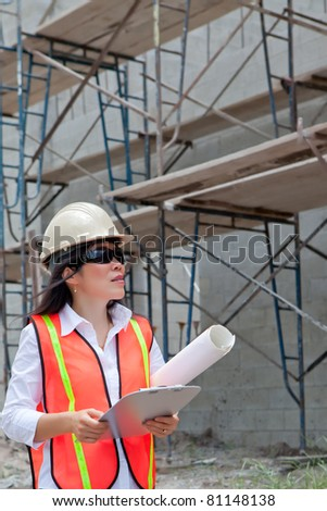 Asian Woman Inspector on construction site. Scaffolding and  block walls in background.