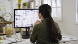asian woman interior designer looking floor plan of new house indoor design on monitor concentrated thinking idea. Blueprint architect construction project sketch concept on laptop computer screen.