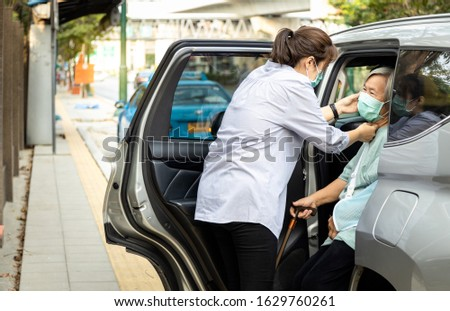 Asian woman is care,help,wearing face mask protection for senior while get out of the car to prevent virus in the air,spread of germ,Coronavirus,worried about air pollution,PM 2.5,dust,bad environment ストックフォト ©