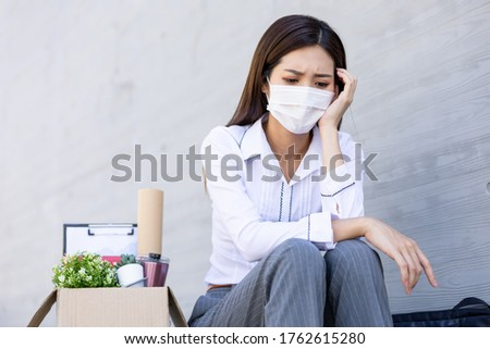 Asian woman is laid off due to COVID-19 and feel upset with faicial mask Stockfoto ©